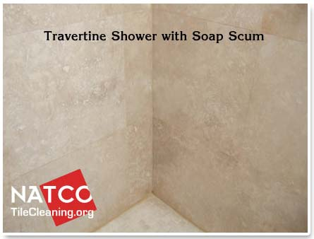 travertine shower with soap scum on it